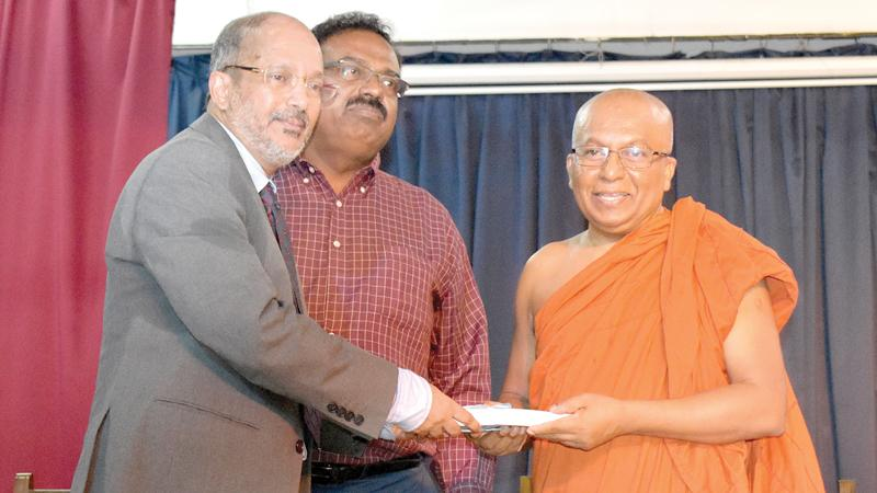 Author Lukman Harees presents the first copy of the book, 'Wisdom at our Doorstep' to Ven. Galkande Dhammananda Thera