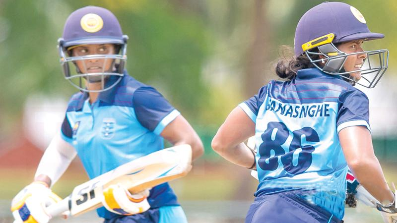 Air Force players Tharuka Shehani (left) and Oshadi Ranasinghe cross for runs during their final League match against Army