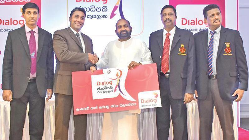Harsha Samaranayake the Senior General Manager - Brand and Media of Dialog, presents the sponsorship cheque to Ranjith Siyambalapitiya MP and president of the Sri Lanka Volleyball Federation as AS Nalaka, General Secretary of the Sri Lanka Volleyball Federation looks on