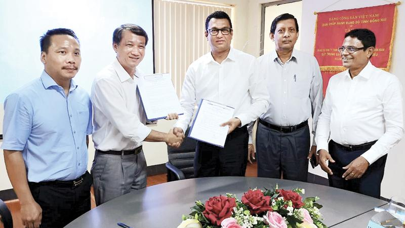 Singer (Sri Lanka) CEO Mahesh Wijewardene and SWEAM Company's General Director Le Viet Hung at the signing of the trade agreement. Singer (Sri Lanka) Marketing Director Kumar Samarasinghe is also in the picture.