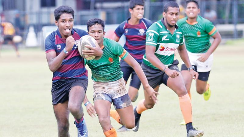 A player from Bandaranayake College runs past an opponent from President's College in Maharagama