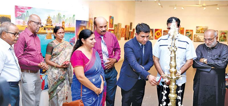 Dr. Revant Vikram Singh, director of the Indian Cultural Centre ceremonially opening the exhibition by lighting the oil lamp. Dr. Monica Sharma, the Hindi language professor at the Cultural Centre, Artist R. Kouwshigan, Mrs. Kowshigan, Chairman of the Colombo Saibaba Centre S. Udhayanayagam, Deputy Chairman Siva Rajajothy, Literary Philosopher Hasim Omar, and Author Memon Kavi are also seen.