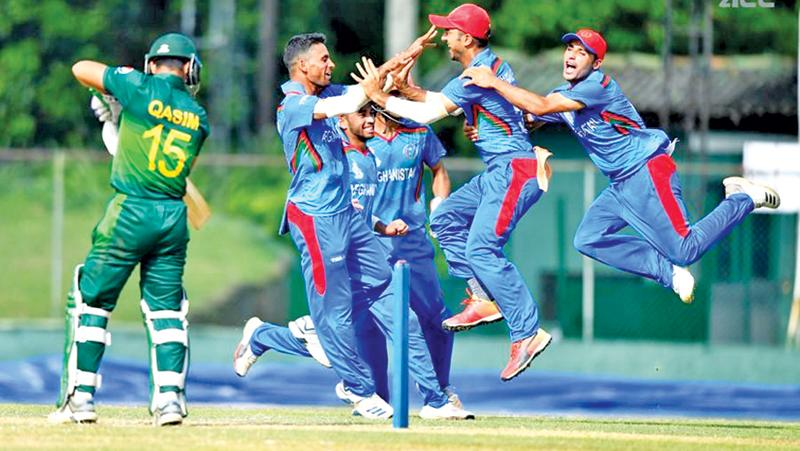 Afghanistan's youth who have never played school cricket jump for joy at the dismissal of Pakistan batsman  Qasim Akram at the P Sara Oval in Colombo. Afghanistan bowed out winners