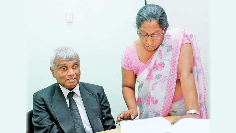 Kanthi Swarnalatha reads out a document aloud to Udayasiri Rajapaksa.             Pic : Roshan Pitipana