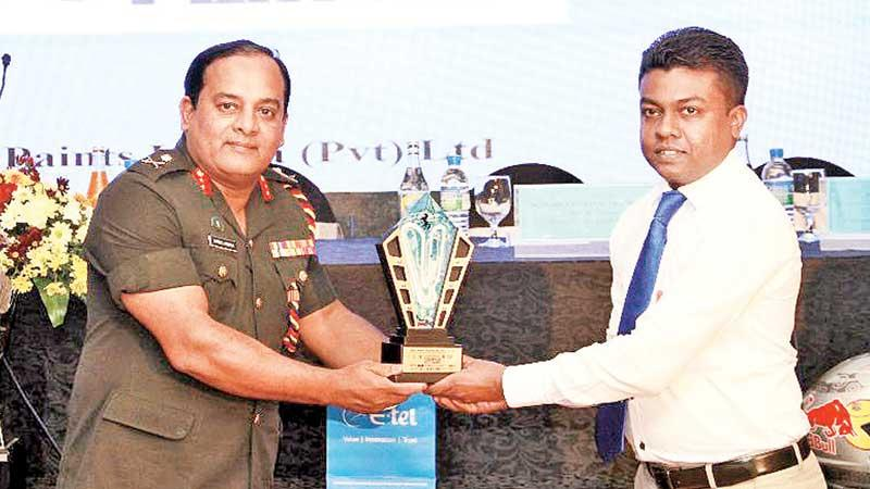 Commandant Duminda Sirinaga receives the Champions Trophy from Pramila Rashan Weeratunga the Deputy General Manager Causeway Paints at the launch of the Walawa Supercross (Pic: Dushmantha Mayadunne)