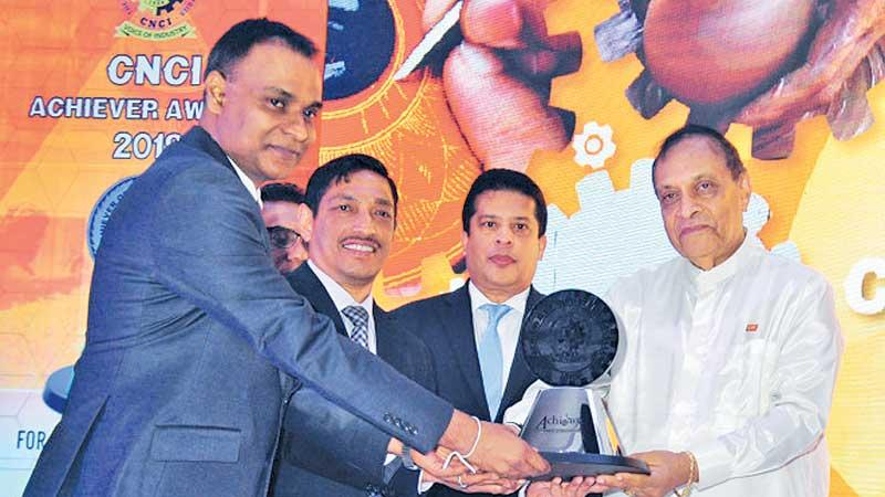 A Royal Ceramics official receives one of the awards from Speaker Karu Jayasuriya.