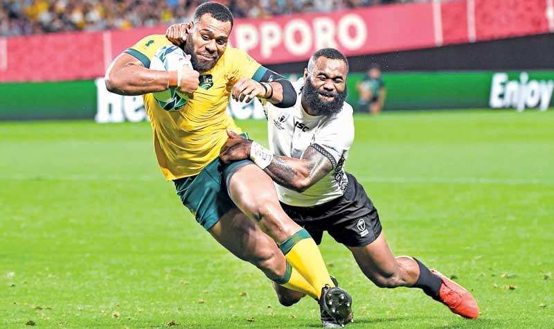 Australia's centre Samu Kerevi goes through to score a try as Fiji's wing Semi Radradra tries to tackle him
