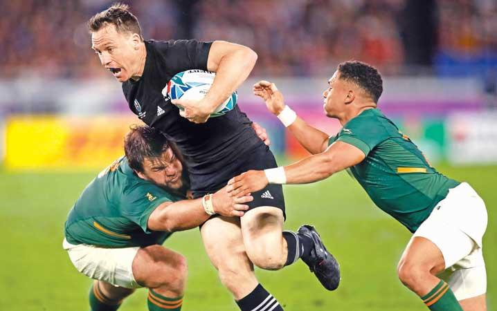 New Zealand's full back Ben Smith (C) attempts to evade a tackle by South Africa's prop Frans Malherbe (L) during their Rugby World Cup Pool B match against South Africa in Yokohama yesterday (AFP)
