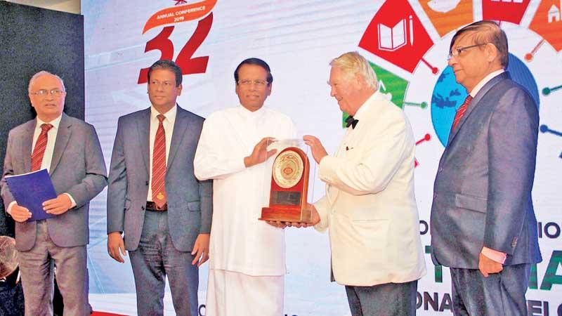 President Maithripala Sirisena presents a token of appreciation to guest of honour former Deputy Speaker, House of Commons, Lord Naseby. Pix: Wimal Karunathilake