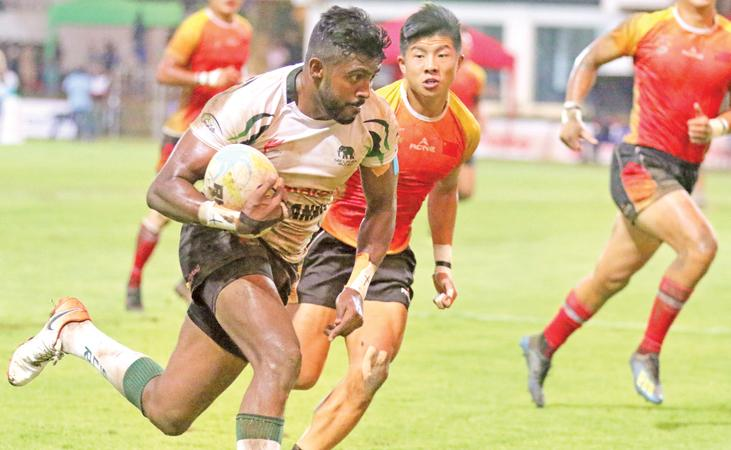 Sri Lanka Sevens captain Dansha Dayan beats the Chinese defence in their Asian rugby series match at the Race Course ground in Colombo last Sunday  (Pic by Saman Sri Wedage)