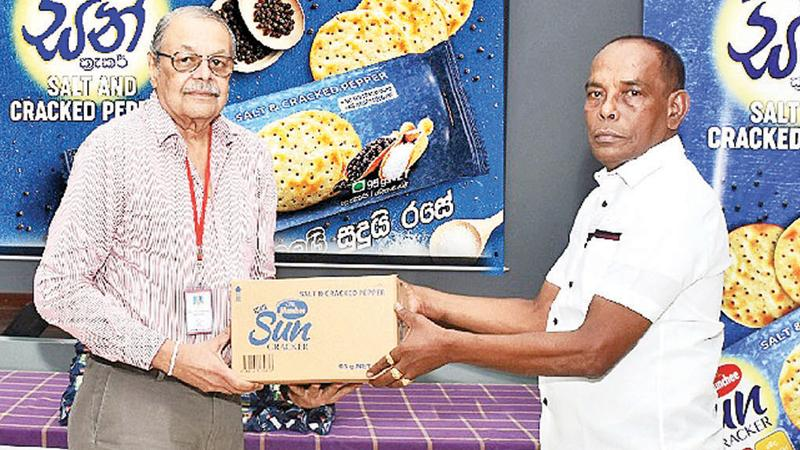 Chairman, Ceylon Biscuits, Ramya Wickramasingha (left)  presents the first consignment of the Munchee Sun Cracker Salt & Cracked Pepper to  Munchee distributor for Homagama, C. Kumarage.