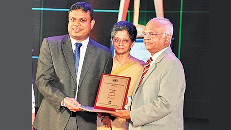 Sirio Production Manager Duminda Sasanapala (second from left)  receives the award from Justice D. J. de S. Balapatabendi. EDB  Chairperson and CEO Indira Malwatte  looks on.