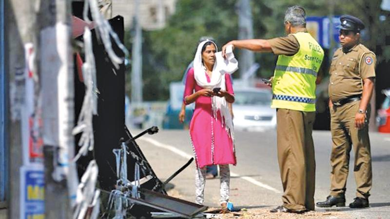 A Muslim woman talks with a police crime officer near her damaged house after a clash between two communities in Digana, Kandy. File pic: Reuters/Dinuka Liyanawatte