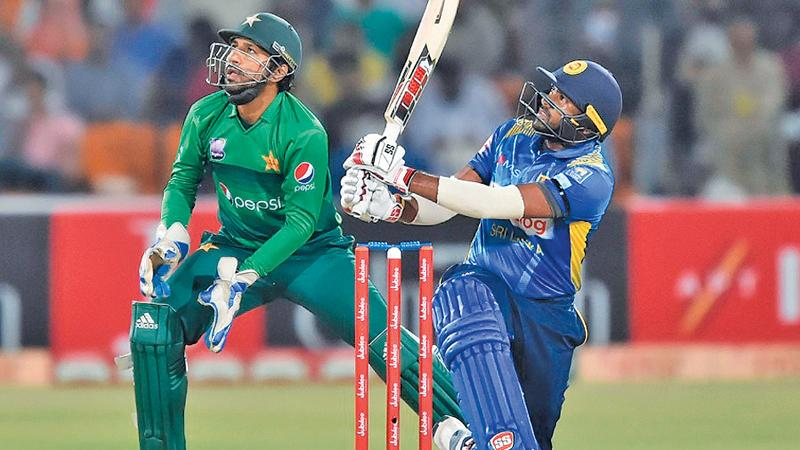 Bhanuka Rajapaksa smashes a six watched by Pakistan wicket-keeper Sarfaraz Ahamed in the recent T20 series