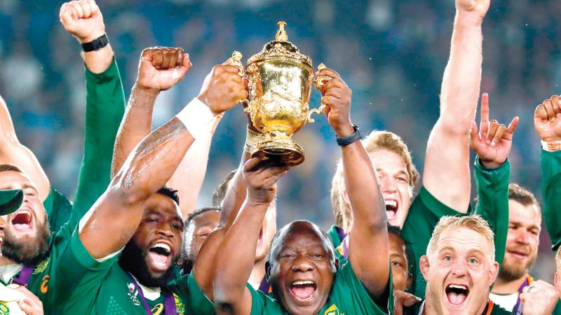 South Africa's captain Siya Kolisi (L) and the country's President Cyril Ramaphosa (C) lift the Webb Ellis Cup as they celebrate winning the World Cup in Japan yesterday (AFP)