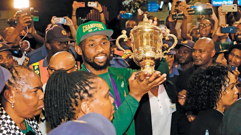 South Africa rugby captain Siya Kolisi carries the Web Ellis World Cup through the crowd upon the team's arrival in Johannesburg (AFP)