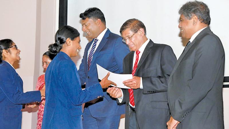 CA Sri Lanka President Jagath Perera presents a scholarship to a student of Musaeus College.