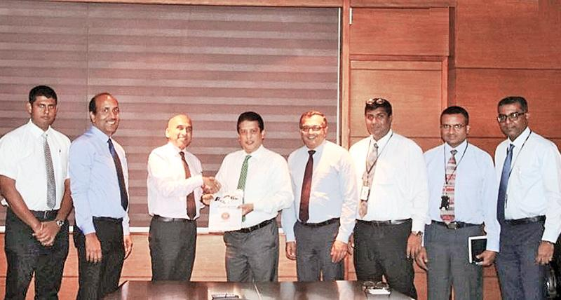 CEO, DFCC Lakshman Silva (fourth from left) and Managing Director LIOC, Manoj Gupta exchange the agreement. Looking on (from left) are Manager, Sales, LIOC,  Surien Gomez, SVP Retail, LIOC, Girish Rajan, Chief Operating Officer, DFCC, Achintha Hewanayake, Head of IT, DFCC, Nishan Weerasooriya, Vice President, Services and Procurement, DFCC, Gaminda Fernando and Assistant Vice President Digital Strategy, DFCC, Dinesh Jebamani.