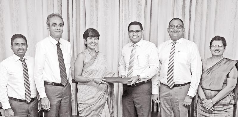 Commercial Bank's Chief Operating Officer Sanath Manatunge (third from right) and Jayanthi Dharmasena, Managing Director of Hayleys Agriculture Holdings exchange the agreement in the presence of (from right), Commercial Bank's Deputy General Manager – Personal Banking Sandra Walgama and Deputy General Manager, Marketing, Hasrath Munasinghe, Hayleys Agriculture Director Amjad Rajap and the company's Deputy General Manager Sumith K. Herath at the signing of the agreement.
