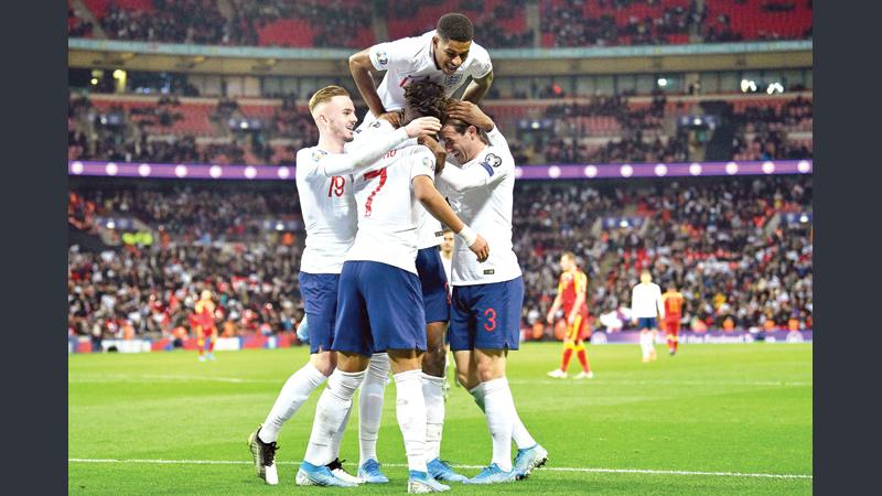 England's striker Tammy Abraham celebrates with teammates after scoring their seventh goal during the UEFA Euro 2020 qualifying first round Group A football match against Montenegro at Wembley Stadium in London (AFP)