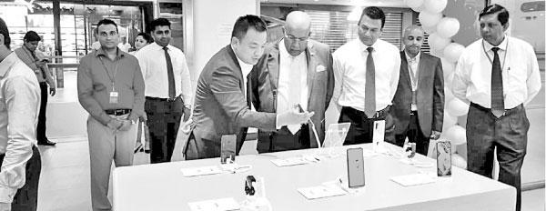 Huawei Device Sri Lanka Country Manager Peter Liu shows the latest Huawei Smartphones to Singer Sri Lanka Group Chairman Mohan Pandithage. Huawei Device Sri Lanka General Manager Kalpa Perera, Singer Sri Lanka Group CEO Mahesh Wijewardene and Singer Sri Lanka PLC Marketing Director Kumar Samarasinghe look on.
