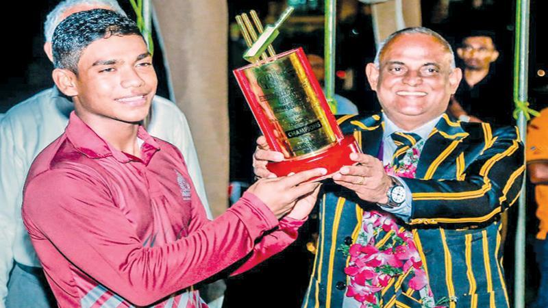 Avishka Perera captain of Nalanda College receiving the champions trophy from Shantha de Silva past cricketer of Mahinda College