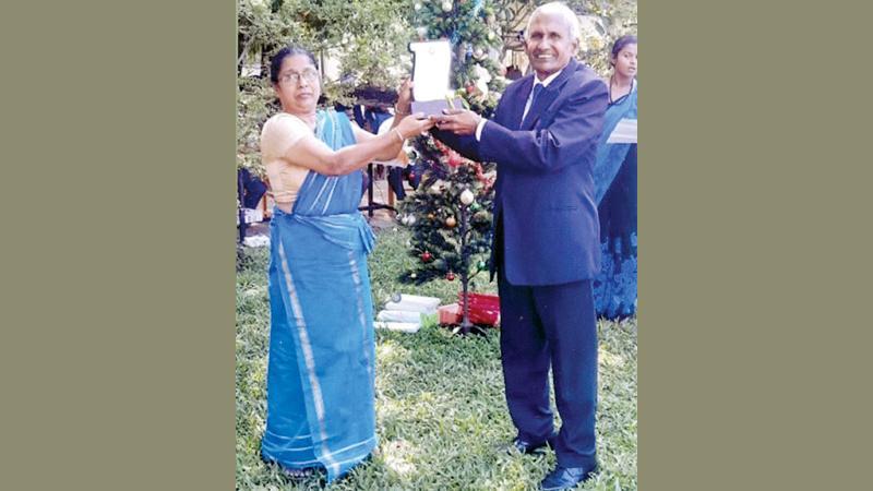 Principal Samanthika Jayasuriya (left) presenting the merit award to Vivekanandan at the felicitation ceremony