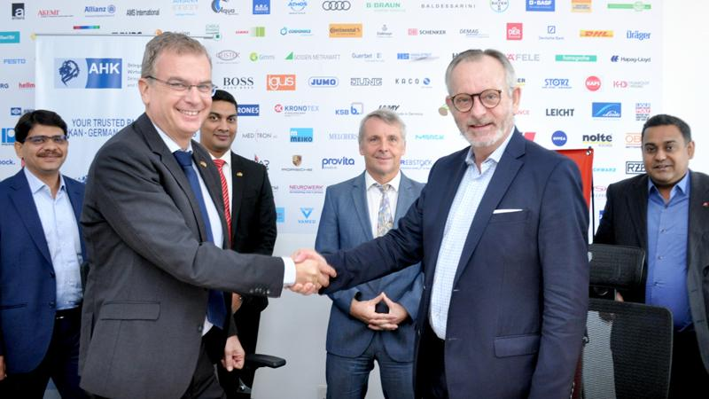 AHK Sri Lanka Chief Delegate Andreas Hergenroether exchanges the agreement  with Hafele South Asia Managing Director Jurgen Wolf while German Ambassador to Sri Lanka Joern Rohde. Hafele officials look on. Pic: Lasantha Kumara
