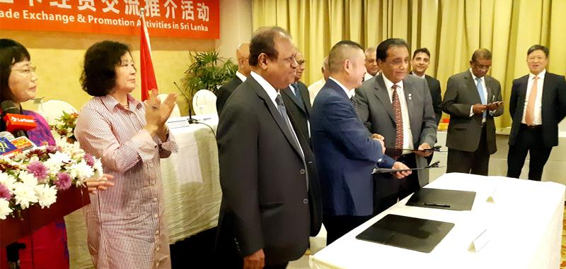 Chairman Mianyang Association of Commerce Zhang Zhongcheng and COSMI Founder President Nawaz Rajabdeen exchange the agreements. Looking on (from left): Secretary General Mianyang Association of Commerce Yuan Wenyan, COSMI founding member Hui Dias Bandaranayake, State Minister of International Cooperation, Susil Premajayantha and Chairman, Mianyang Enterprise Union for Import and Export, John Luo (far right).