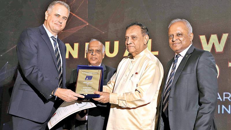 Koenraad Pringiers receives a merit award from Speaker Karu Jayasuriya.  Chairman Admin and Finance Sub-committee, Ananda Caldera (second from left) and President, PRISL, Kaushal Rajapaksa (fourth from left) look on.