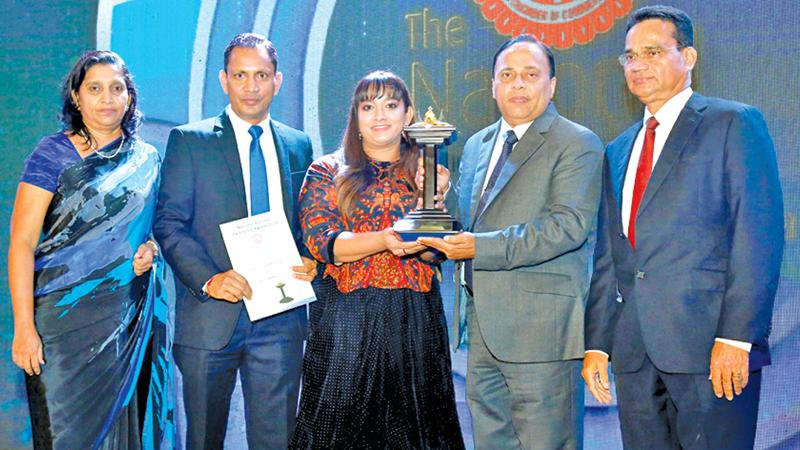 Aitken Spence Hotels team receiving an award from DGM, Advertising, Lake House, Varuna Mallawaarachchi at the 55th Annual Report Awards.