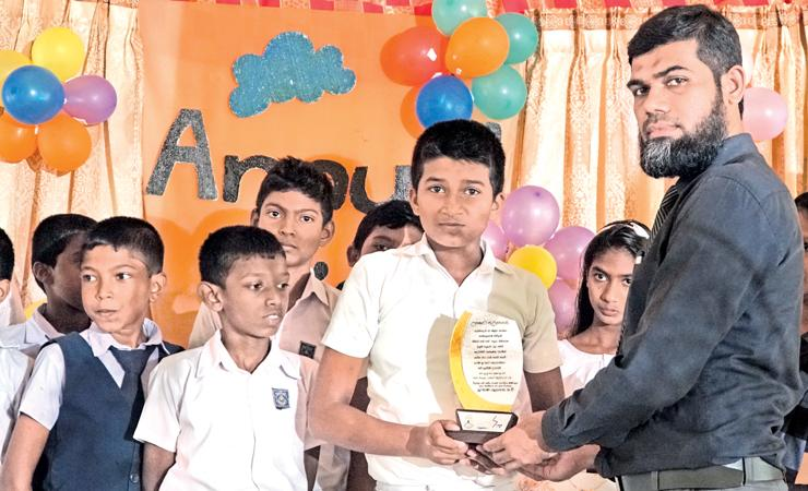 SLT Regional Manager, Puttalam, M. A. M. Ziyam presents gifts to students.