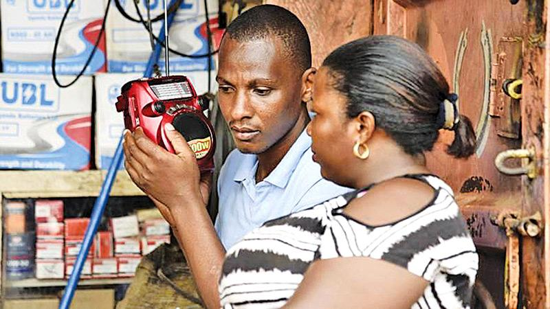People listen to the radio as the results of the presidential election is announced in Kireka, Uganda, in February. Many rural Ugandans don't have Internet access, and the radio is a central source of news -- and platform for citizens' opinions