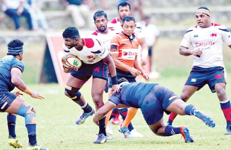 Kandy SC's Soyuru Anthony attempts to break away from a Navy tackle (Pix Shan Rambukwella)