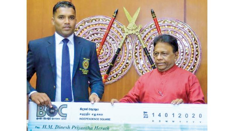 Champion Para athlete Dinesh Herath receiving Rs. 4.2 million award from  the Sport Minister Dullas Alahapperuma at the Sport Ministry