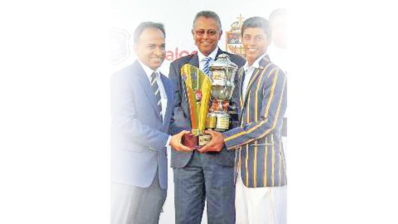 Danal Hemananda (right) of St. Peter's College receives the best allrounder's trophy from Munesh David the vice president of Dialog Axiata at the conclusion of the drawn Battle of the Saints big match cricket encounter against St. Joseph's College at the P Sara Oval in Colombo yesterday