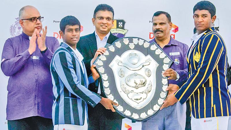 Thevin Eriyagama the captain of S. Thomas' College (left) and Thevindu Senaratne the captain of Royal College hold the DS Senanayake Shield that was presented by Supun Weerasinghe the Group Chief Executive Officer of Dialog Axiata after their 141st big match ended in a draw at the SSC ground yesterday in the presence of Rev. Marc Billimoria (left) warden of S. Thomas' College and BA Abeyratne the principal of Royal College