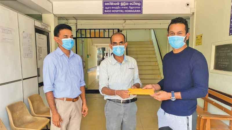 Dimuth Karunaratne (right) makes the donation on behalf of  his team to Dr. Janitha Hettiarachchi, Medical Superintendent of the Homagama Base Hospital