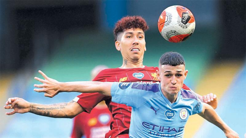 Liverpool's Brazilian midfielder Roberto Firmino (L) vies with Manchester City's English midfielder Phil Foden (R) during the English Premier League football match on July 2, 2020. ( AFP)