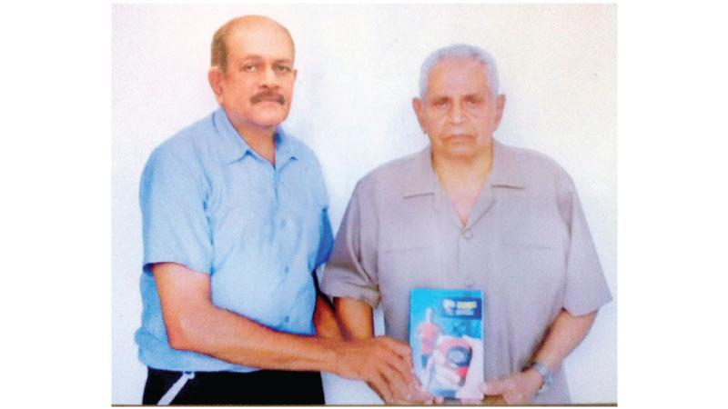 Pictured here is Gunawardena (left), presenting the first copy of the book to former National shot put champion and senior  athletics coach of the Sports Ministry, AJ Rodrigo (Sr)