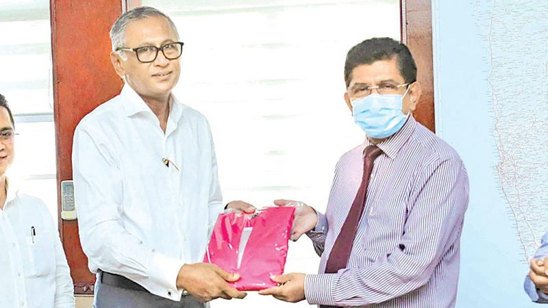 Executive Director, Emerald International, M.M.M. Ihsan makes a token presentation of the face masks to Director-General of Health Services, Dr. Anil Jasinghe.
