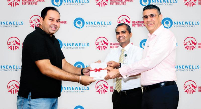 AIA CEO Nikhil Advani and Ninewells Chief Operating Officer and Medical Director Dr. Vibash Wijeratne presents the first complimentary AIA Life Cover to a new parent at Ninewells.