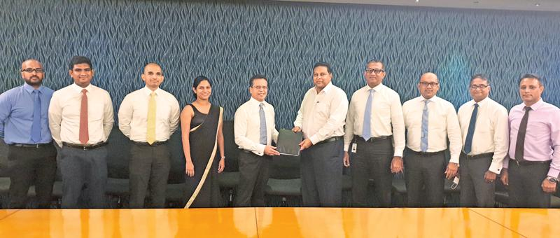 CEO, Union Assurance, Jude Gomes presents the Group Life Cover to Priyantha Talwatte, Director and CEO, Nations Trust Bank. The management teams of Nations Trust Bank and Union Assurance look on.