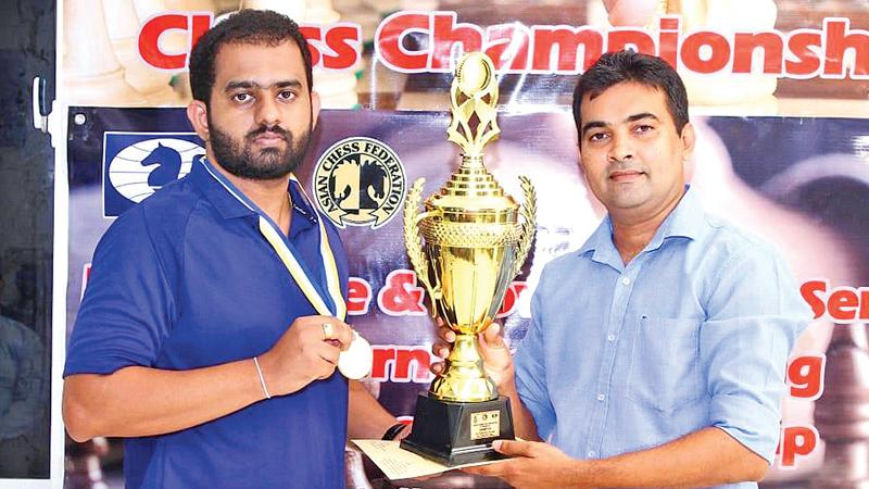 99X Technology Application Security Engineer Pranieth Chandrasekara (left) receives the trophy from Chess Federation of Sri Lanka Treasurer Irosh Jayasinghe.