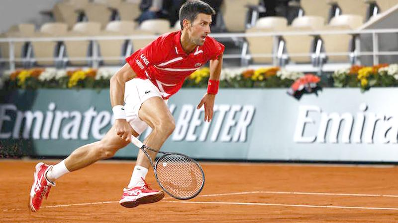 Serbia's Novak Djokovic runs to return the ball to Greece's Stefanos Tsitsipas during their men's singles semi-final tennis match at French Open (AFP)