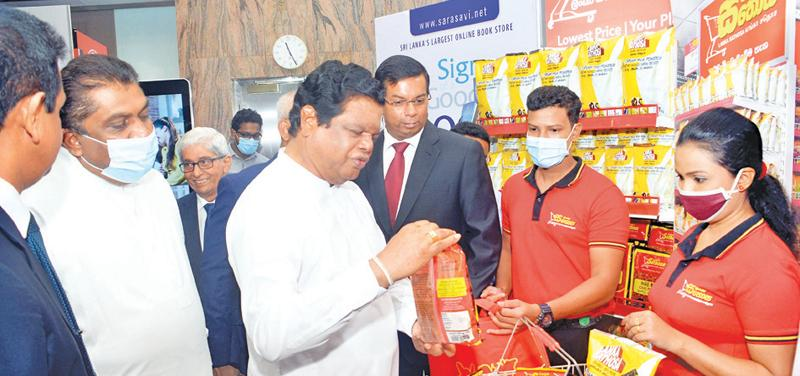 Minister of Trade Bandula Gunawardena makes a purchase at the Lanka Sathosa stall using a LankaQR enabled app. Pic: Wasitha Patabendige