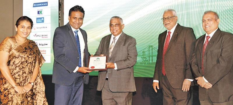 Deputy General Manager, Marketing of People's Leasing, Laksanda Gunawardena  receives the award for One of the Best Ten CSR and Sustainability Projects from  Trustee of  JASTECA, Athula Edirisinghe.   JASTECA President,  Nimal Perera and  Committee Member Nishan Fernando look on.
