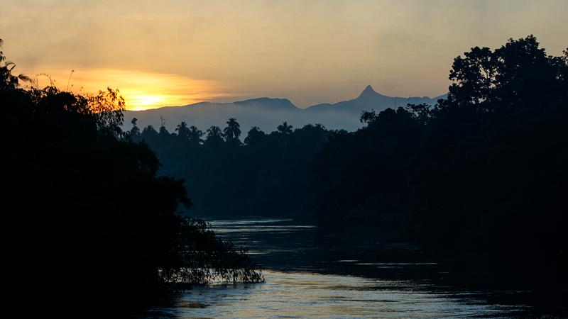 Sunrise over the Sri Pada mountain range seen through Kelani Ganga at dawn in Hanwella