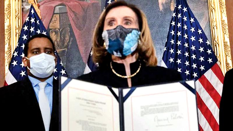 US House Speaker Nancy Pelosi displays the signed article of impeachment against President Donald Trump. The impeachment will now be sent to the Senate for trial