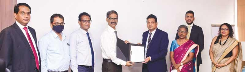 The exchange of the agreement: From left - CEO, NDB Investment Bank, Darshan Perera, Country Head, Indian Overseas Bank, Shameer,  Senior DGM,  NSB, K. Raveendran, CEO, Indian Bank,  Basheer Ahamed,   GM and CEO, NSB, Ajith Peiris, DGM, Credit and International Banking, NSB, Ms. Christine Jesudian, Senior Director, Alpen Capital (ME) Ltd., Dilip Samanthilake and COO, NDB Investment Bank, Ms. Kaushini Laksumanage.